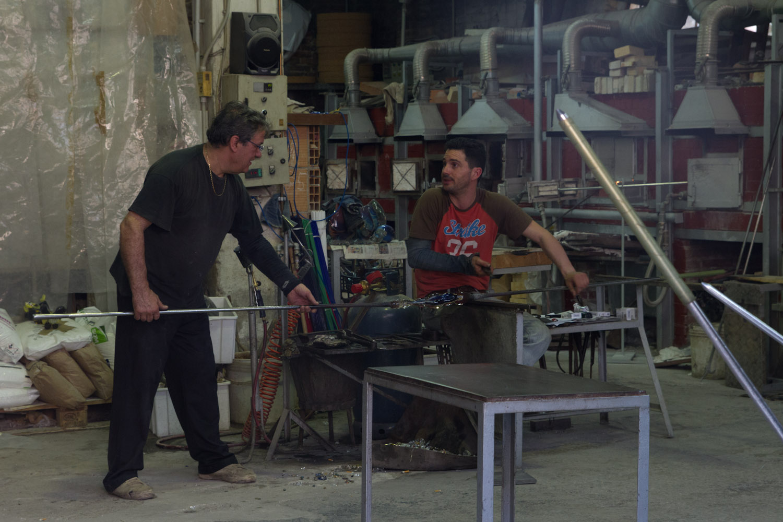 Dos artesanos en plena faena en un taller de cristal de Murano, Italia