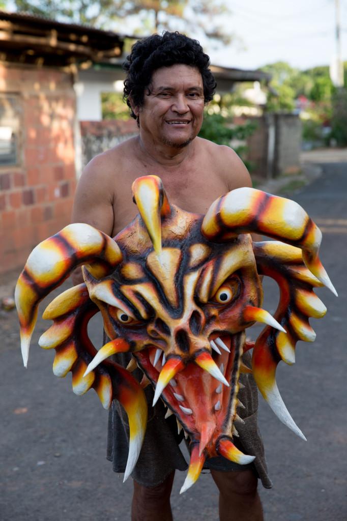 José González posa junto a una de sus máscaras fuera de su taller